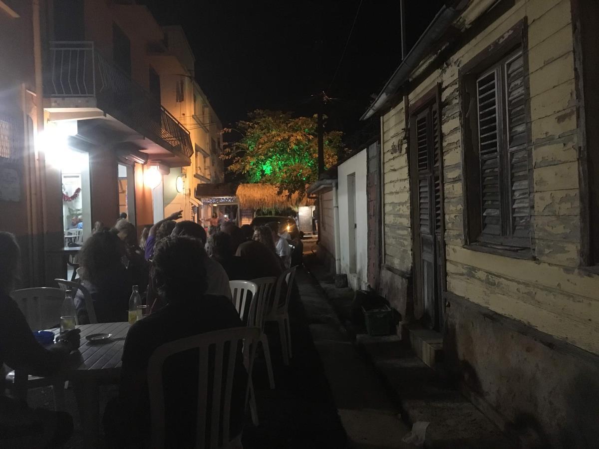 Några plastbord och stolar på gatan och middagen är serverad.